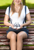 Pregnant woman sitting on bench at park and holding baby shoes Royalty Free Stock Photography