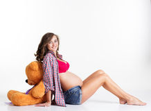 Pregnant woman is sitting with big teddy bear in Royalty Free Stock Image