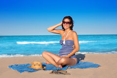 Pregnant woman sitting on blue beach sand Royalty Free Stock Photography
