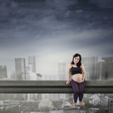Pregnant woman sitting on a bridge Stock Images