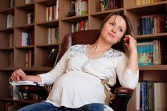 Pregnant woman sitting on a chair Stock Photo