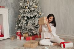 A pregnant woman sitting by the Christmas tree opens Christmas presents royalty free stock images