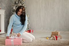 A pregnant woman sitting by the Christmas tree opens Christmas presents royalty free stock image