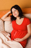 Pregnant woman sitting on the couch Stock Images