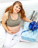 Pregnant woman sitting on couch with gift for baby Stock Photo