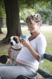 Pregnant Woman Sitting With Dog On Park Bench Royalty Free Stock Images