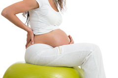 Pregnant woman sitting on fit ball with hand on her back Stock Photos