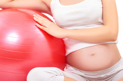 Pregnant woman sitting with fitball, closeup royalty free stock photography