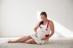 A pregnant woman sitting on the floor talking with a baby in the belly. A pregnant woman sitting on the floor razovarivaet with a baby in the belly Royalty Free Stock Photos