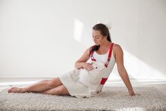 A pregnant woman sitting on the floor talking with a baby in the belly stock photos