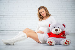 Pregnant woman sitting on the floor with a teddy bear Royalty Free Stock Image