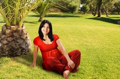 Pregnant woman sitting on the grass Royalty Free Stock Photography