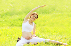 Pregnant woman sitting on the grass doing fitness or yoga Royalty Free Stock Photography