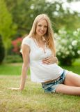 Pregnant woman sitting on grass Royalty Free Stock Image