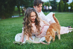 Pregnant woman sitting on the grass and stroking her stomach Stock Photo