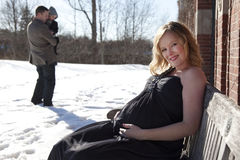 Pregnant woman sitting at house. A pregnant woman sitting next to a house with her family in the background in wintertime Stock Photos