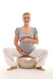 Pregnant woman sitting on large exercise ball Stock Image