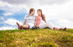 Pregnant woman sitting on lawn with husband Stock Images