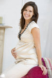 Pregnant woman sitting in living room smiling Royalty Free Stock Image