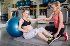 Pregnant woman sitting on mat with her personal trainer Royalty Free Stock Image