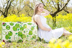 Pregnant woman is sitting near suitcase Royalty Free Stock Image