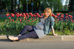 Pregnant woman sitting near tulip Royalty Free Stock Photography