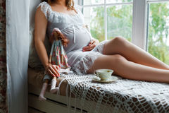 Pregnant woman sitting near the window Stock Image