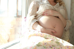Pregnant woman sitting near the window Royalty Free Stock Photography