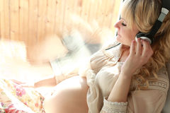 Pregnant woman sitting near the window. Pretty pregnant beautiful girl with white curly hair stock photo