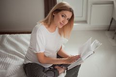 Pregnant Woman Sitting On Bed Touching Her Belly And Reading Book. Expecting Mother Relaxing On Bed Ready A Book. Royalty Free Stock Photo