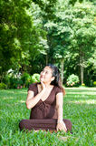 Pregnant woman sitting in the park . in anticipation of the chil Stock Photos