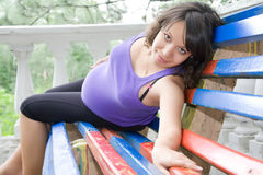 Pregnant woman sitting on park bench Royalty Free Stock Images