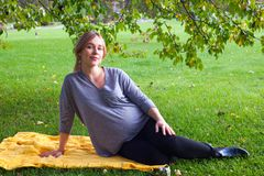 Pregnant woman sitting in the park on the yellow knitted plaid in warm summer or autumn day. Pregnant woman sitting in the park on the yellow knitted plaid in royalty free stock photos