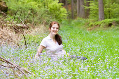 Pregnant woman sitting in a purple flowers field Stock Photos