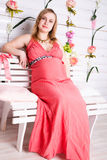 Pregnant woman sitting in the red dress Stock Photos