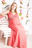 Pregnant woman sitting in the red dress Royalty Free Stock Images