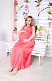 Pregnant woman sitting in the red dress Stock Photography