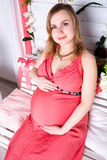 Pregnant woman sitting in the red dress Royalty Free Stock Photo