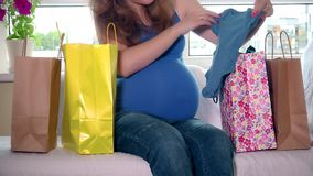 Pregnant woman sitting between shopping bags and stroking her big belly stock footage