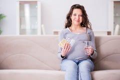 The pregnant woman sitting on sofa Royalty Free Stock Photos