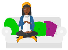 Pregnant woman sitting on sofa. Royalty Free Stock Photography