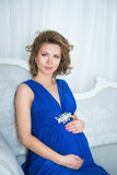 Pregnant woman sitting on the sofa in blue dress Royalty Free Stock Image