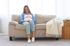 Pregnant woman sitting on sofa in casual comfortable clothes Royalty Free Stock Photos