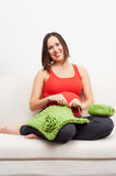 Pregnant woman sitting on sofa and crocheting Royalty Free Stock Images