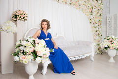 Pregnant woman sitting on the sofa with flowers Royalty Free Stock Photos