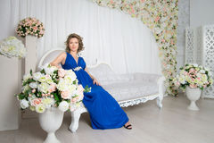 Pregnant woman sitting on the sofa with flowers Royalty Free Stock Photo