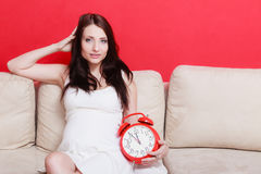Pregnant woman sitting on sofa holding clock Royalty Free Stock Image