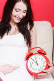 Pregnant woman sitting on sofa holding clock Royalty Free Stock Photo