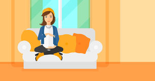 Pregnant woman sitting on sofa. Royalty Free Stock Image