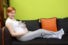 Pregnant woman sitting on sofa with teddy bear Stock Photo